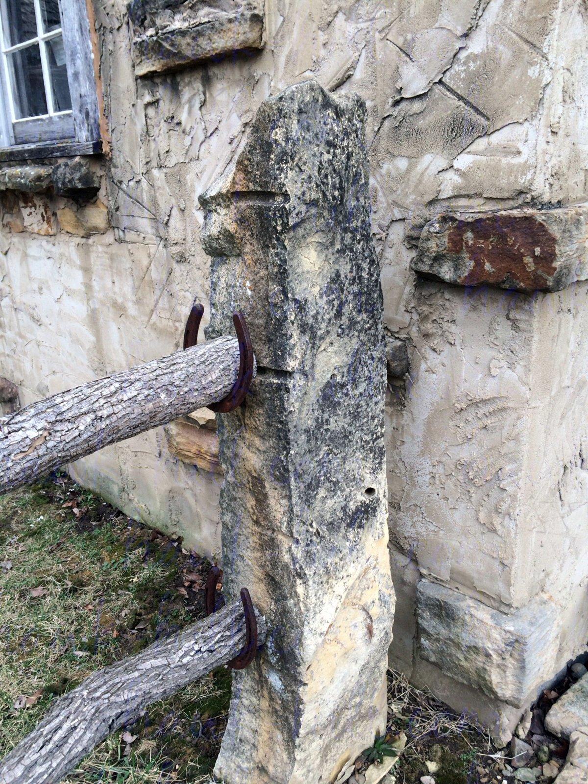 Stone fence post with horseshoe rail bracket.