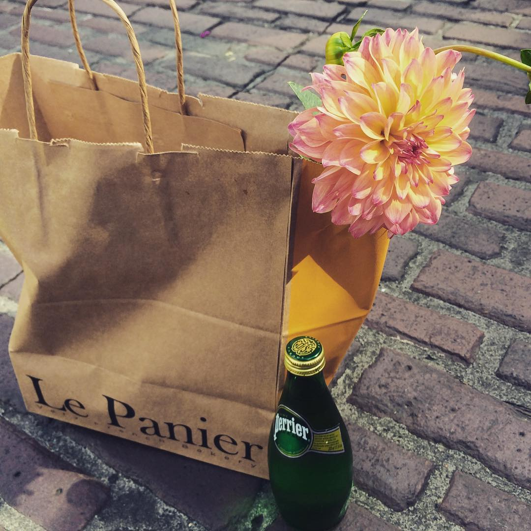 A bag from pike place market's le panier with a flower and bottled water.