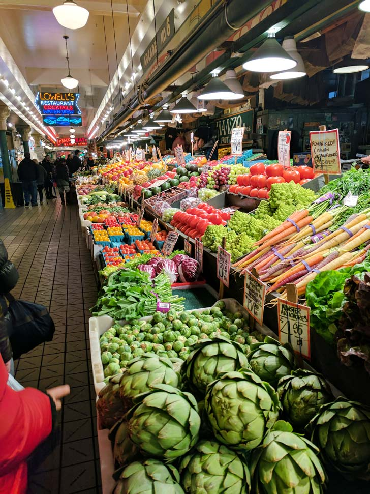 Fruit lined up at pike place market shows that  shopping local markets is a way to experience travel while eating a little healthier.