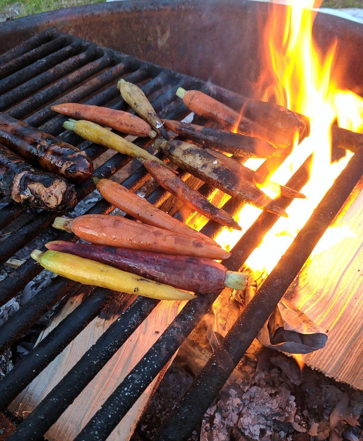Carrots and sausages cooking over an open fire.