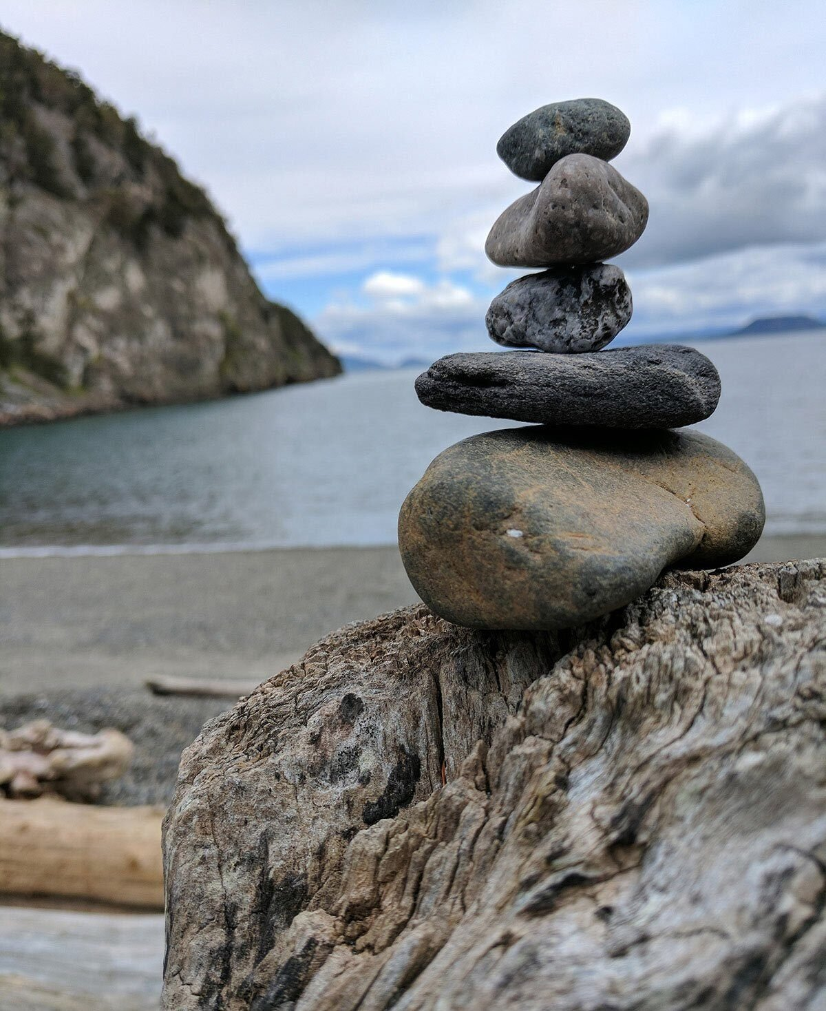 Stacked rocks on driftwood on a pnw beach.