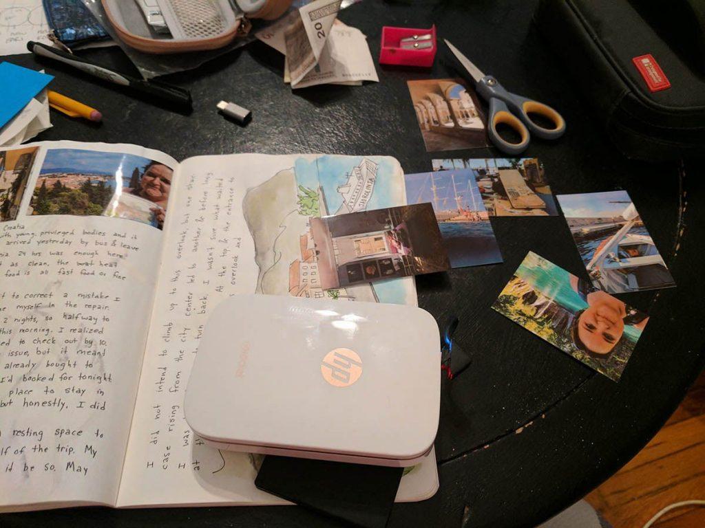 A portable printer printing photos for a travel scrapbook.