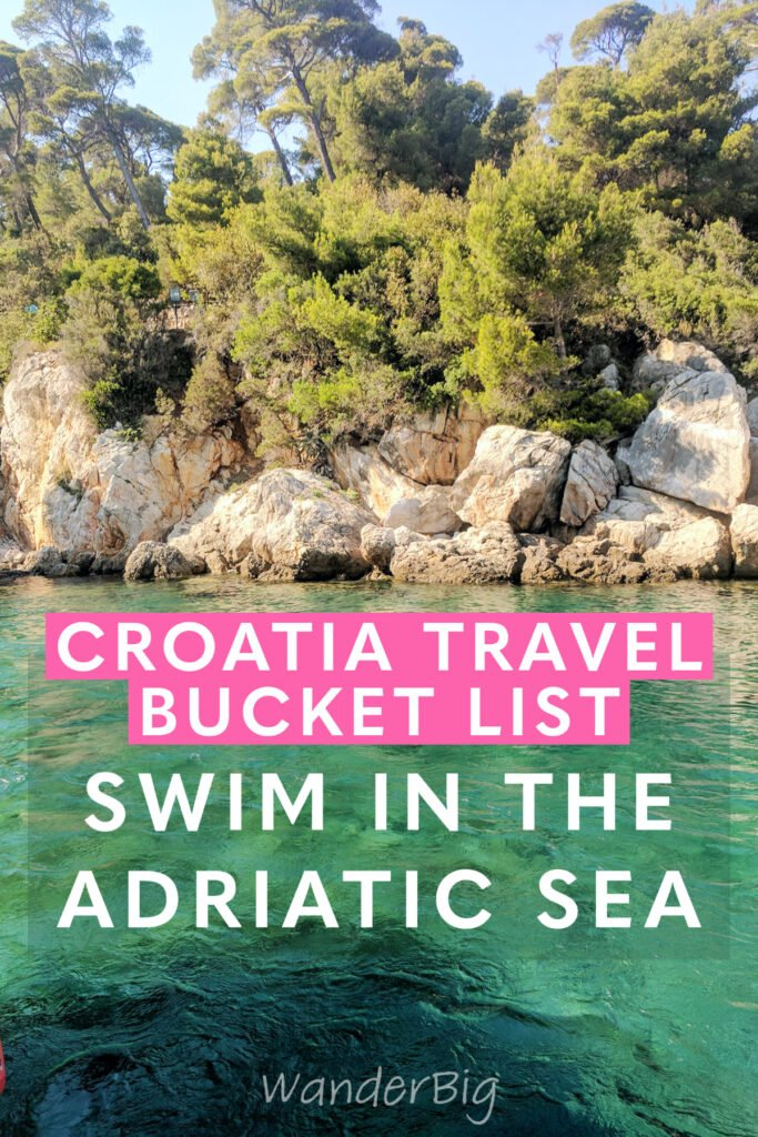 Turquoise green waters of the adriatic sea with craggy rocks and trees.