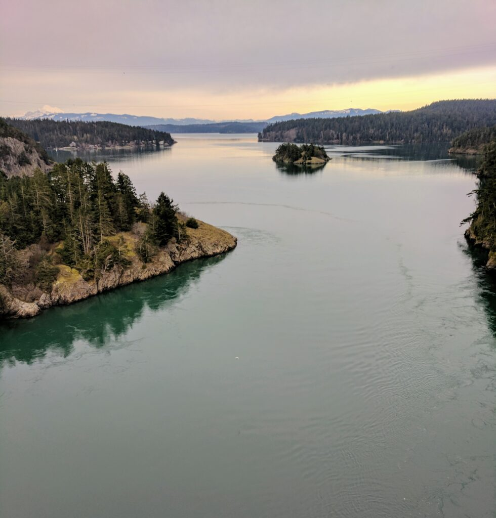 View from deception pass bridge on whidbey island showing water and mountains.