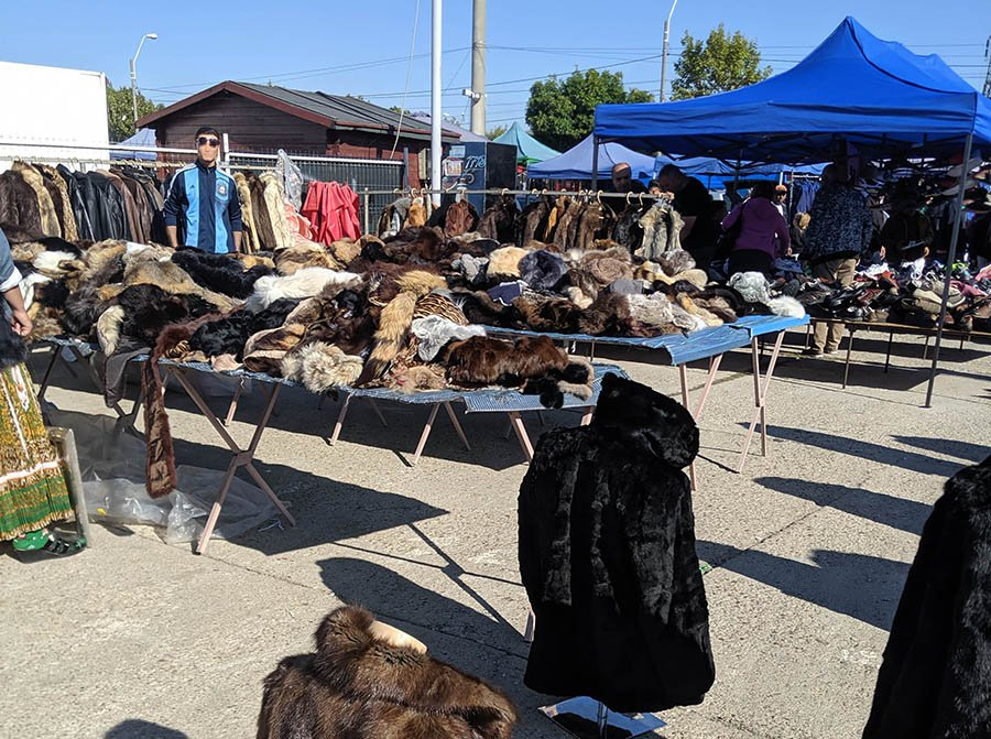 A booth full of used fur coats at an outdoor flea market in bucharest romania