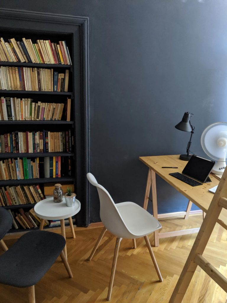 A workspace in a modern short term rental with a molded chair and unfinished table.