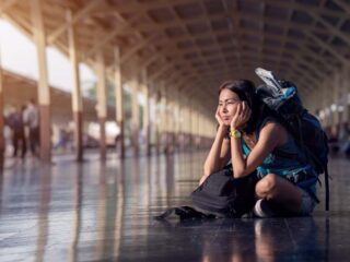 A woman with a weary expression sits on the floor of a train station with her luggage