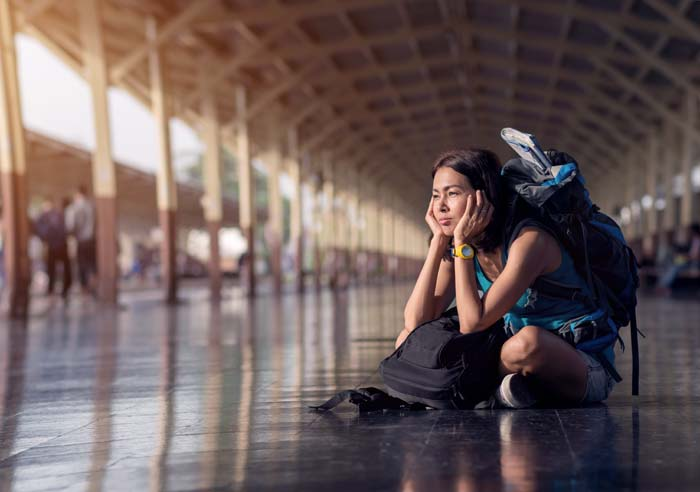 A woman weary from travel burnout sits on the floor of a train station with her luggage