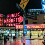 Neon signs illuminated at pike place market after dark.