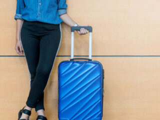 A woman shown from the waist down, standing next to a blue carry-on sized suitcase.