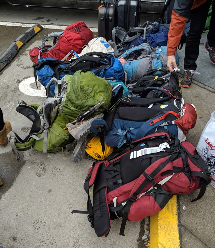 A pile of backpacks on a curb in South America