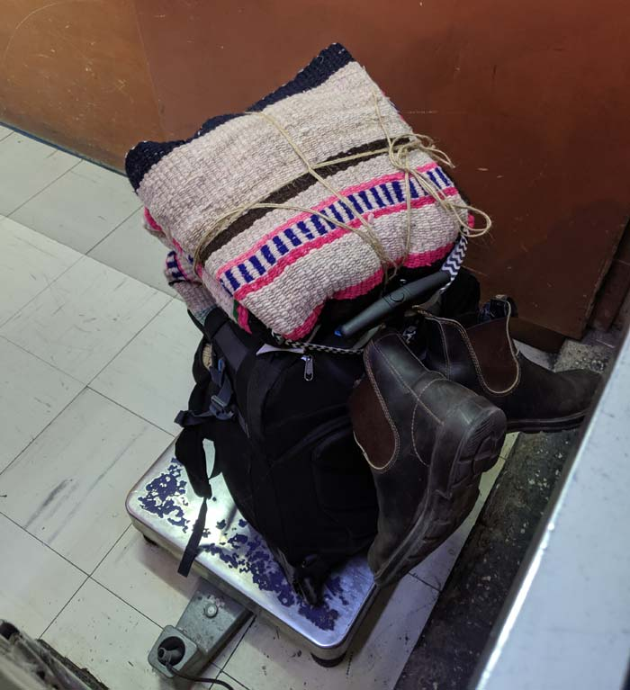 A small carry-on bag with a souvenir blanket on top of a scale at a bus station