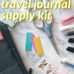 Instructions for packing a compact bullet journaling kit for making a travel journal. Image description: pens, scissors, and other bullet journal supplies spread out on a table.