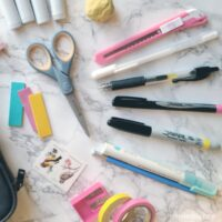 Pens, scissors, and other bullet journal supplies spread out on a table.