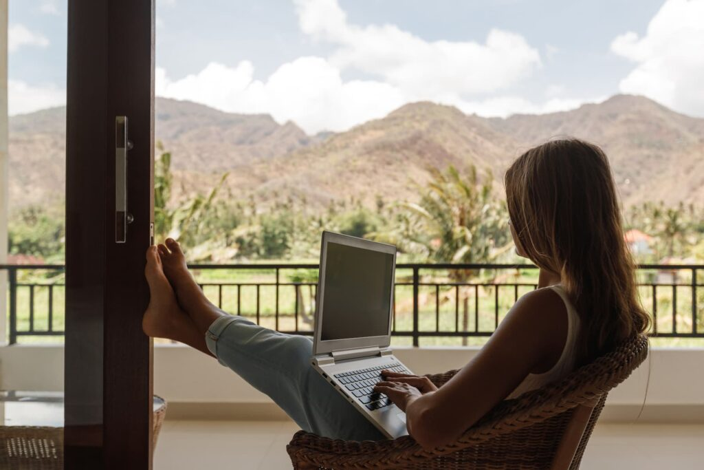Woman working on a computer on a balcony.