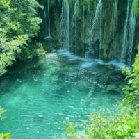 Tropical-looking blue green waterfall in Plitvice National Park.