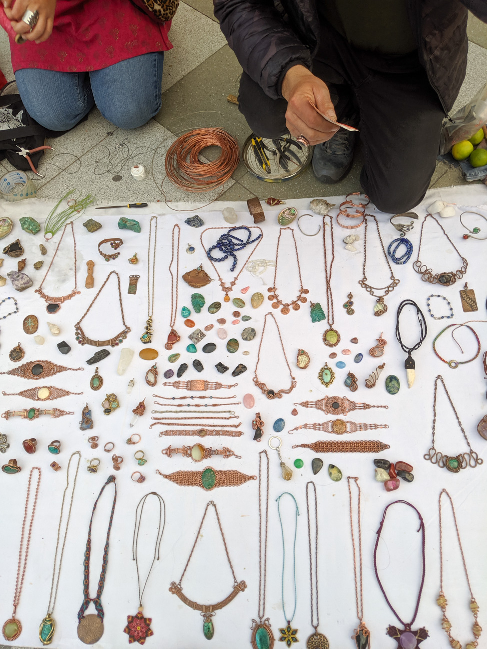 Handmade necklaces spread on a blanket, near a traveler with jewelry making supplies.