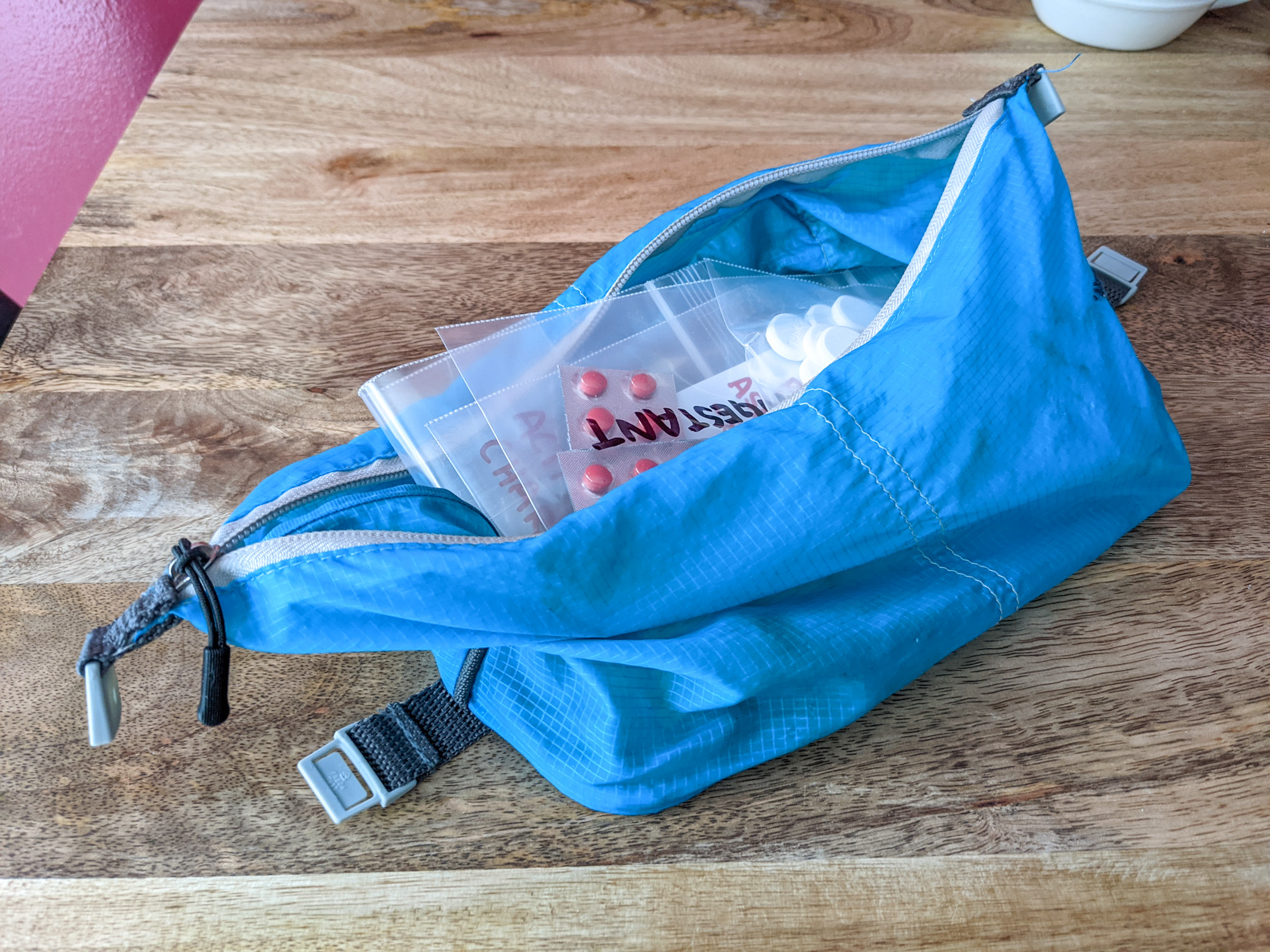 Supplements in a blue bag illustrate how to pack vitamins and supplements for travel.