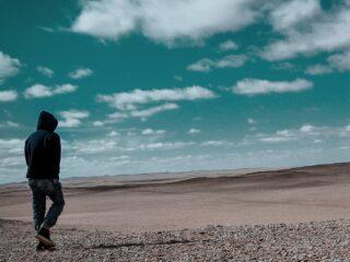 A person in a hooded sweatshirt walks alone in a desert landscape.