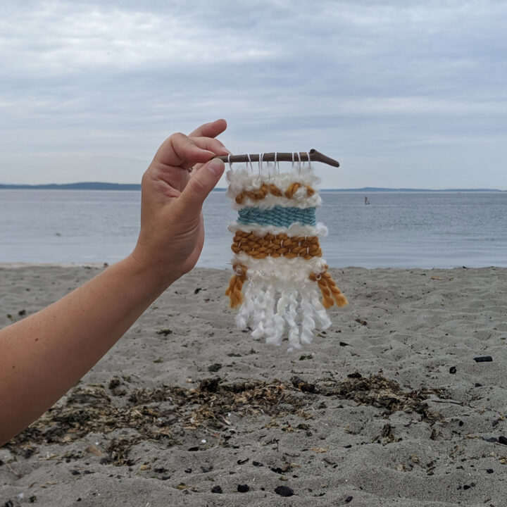 A tiny handmade weaving being held up on a beach.