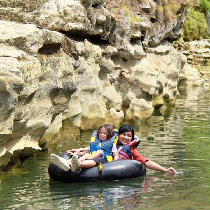 An adult and child float past a rock formation on an inflatable tube.