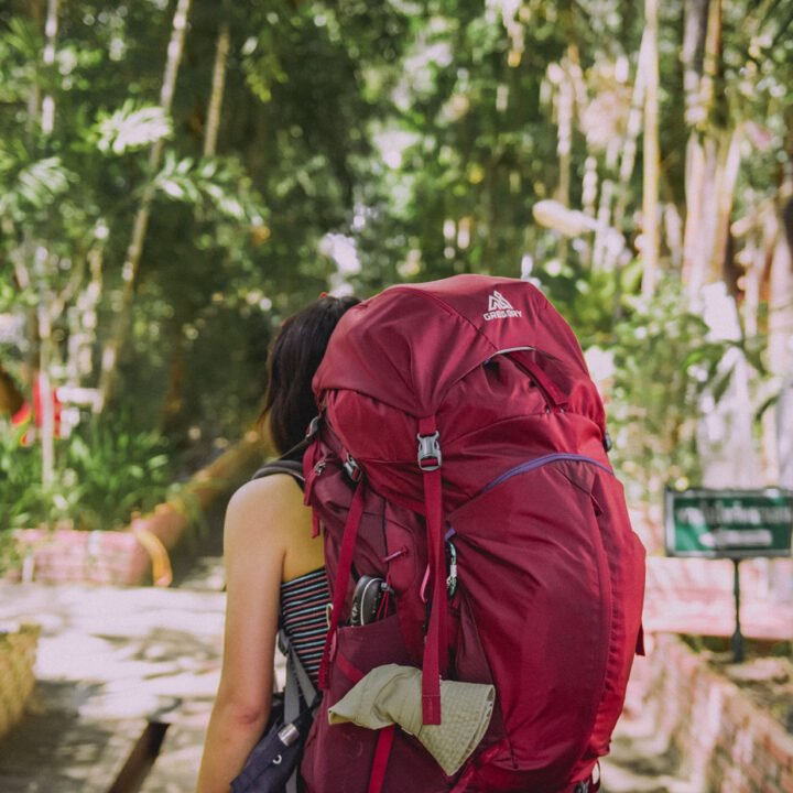 A woman with a large backpack walks in a forested area.