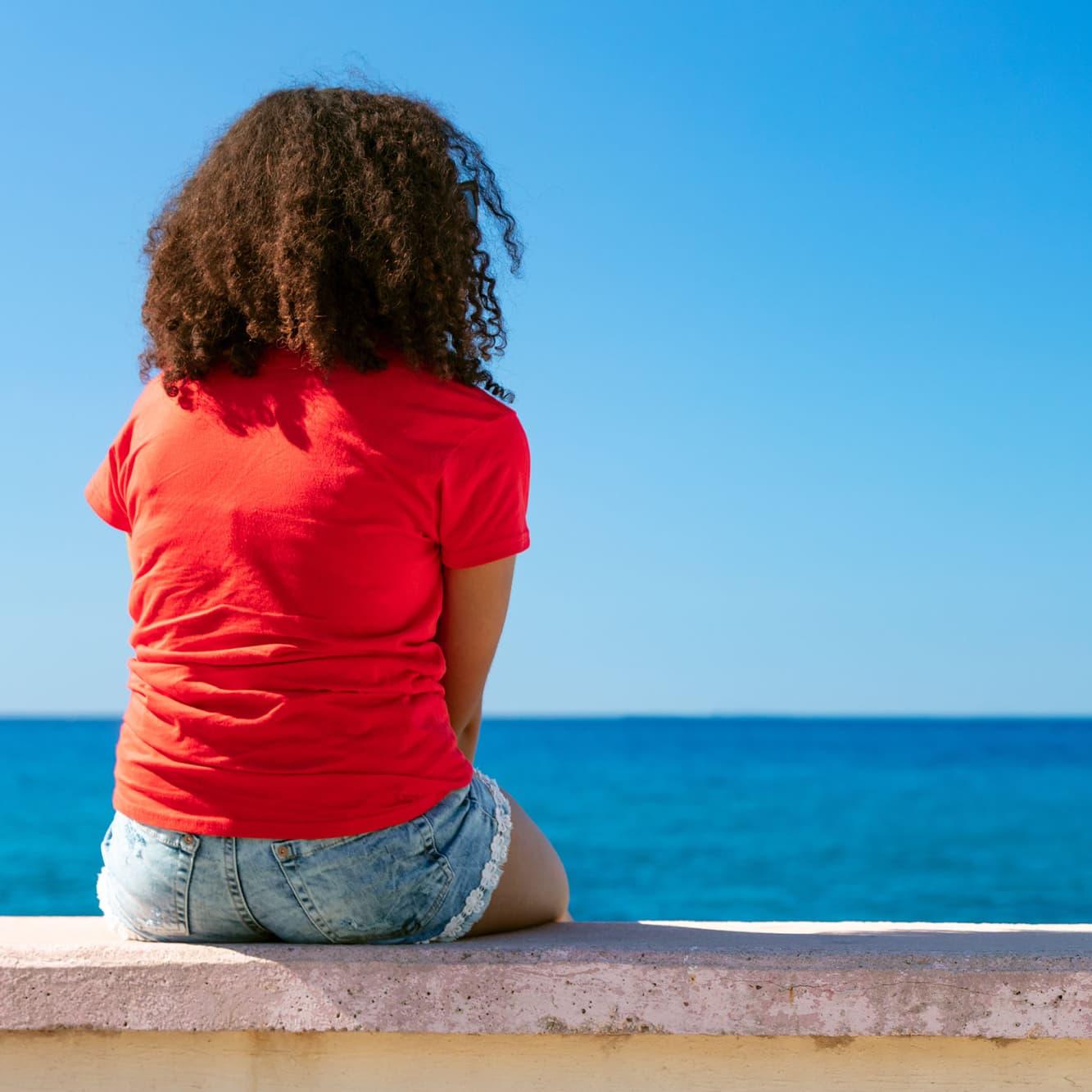 A woman sits on a wall alone near the sea.