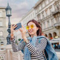 A woman takes a selfie photograph in an urban backdrop.