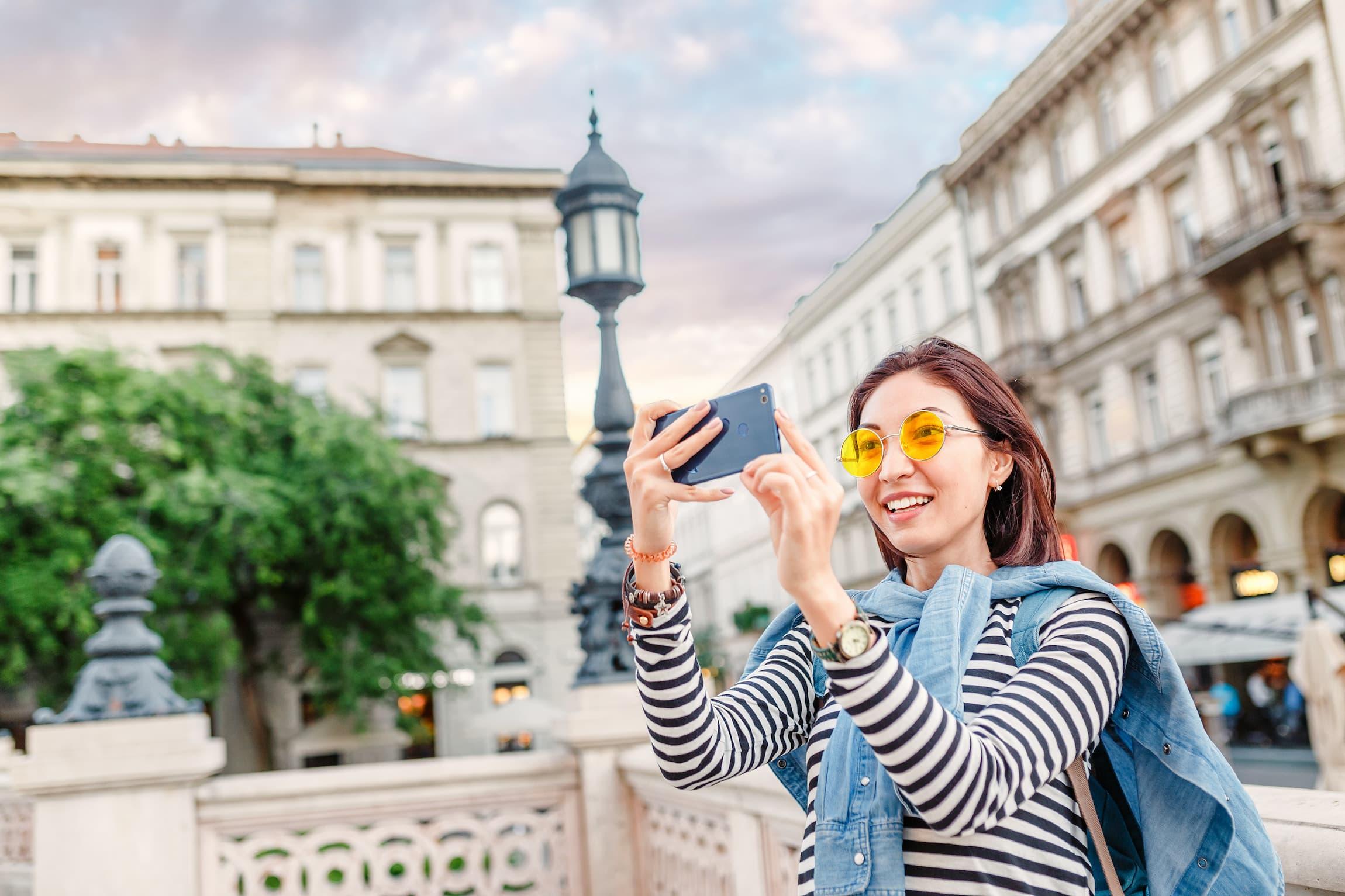 A woman takes a selfie photo in an urban backdrop.