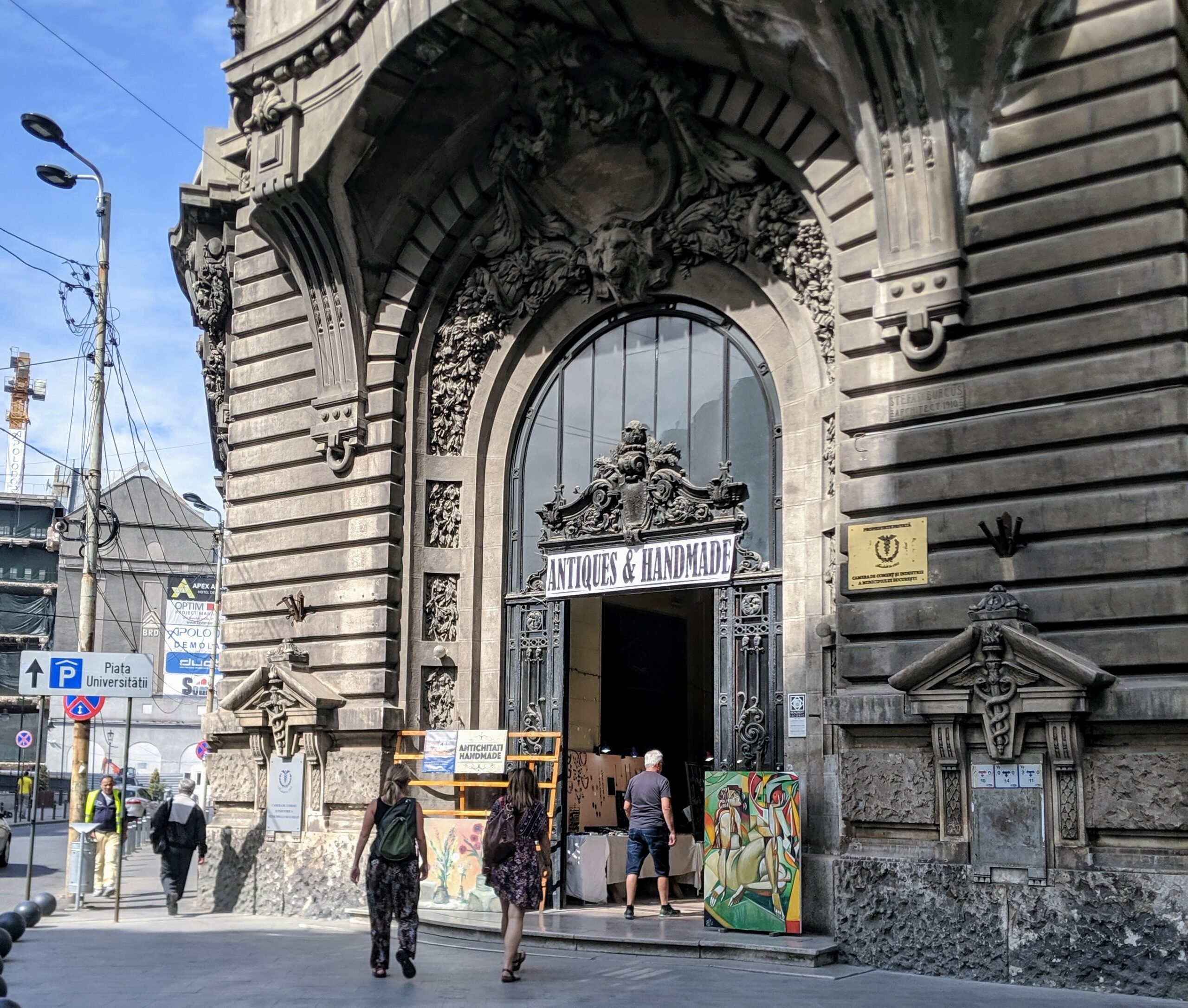 People walking into an old building with a sign that says antiques and handmade, where the purchase of handmade goods can be part of sustainable travel.