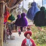 A female weaver in peru walks past a bunting made of tassels.