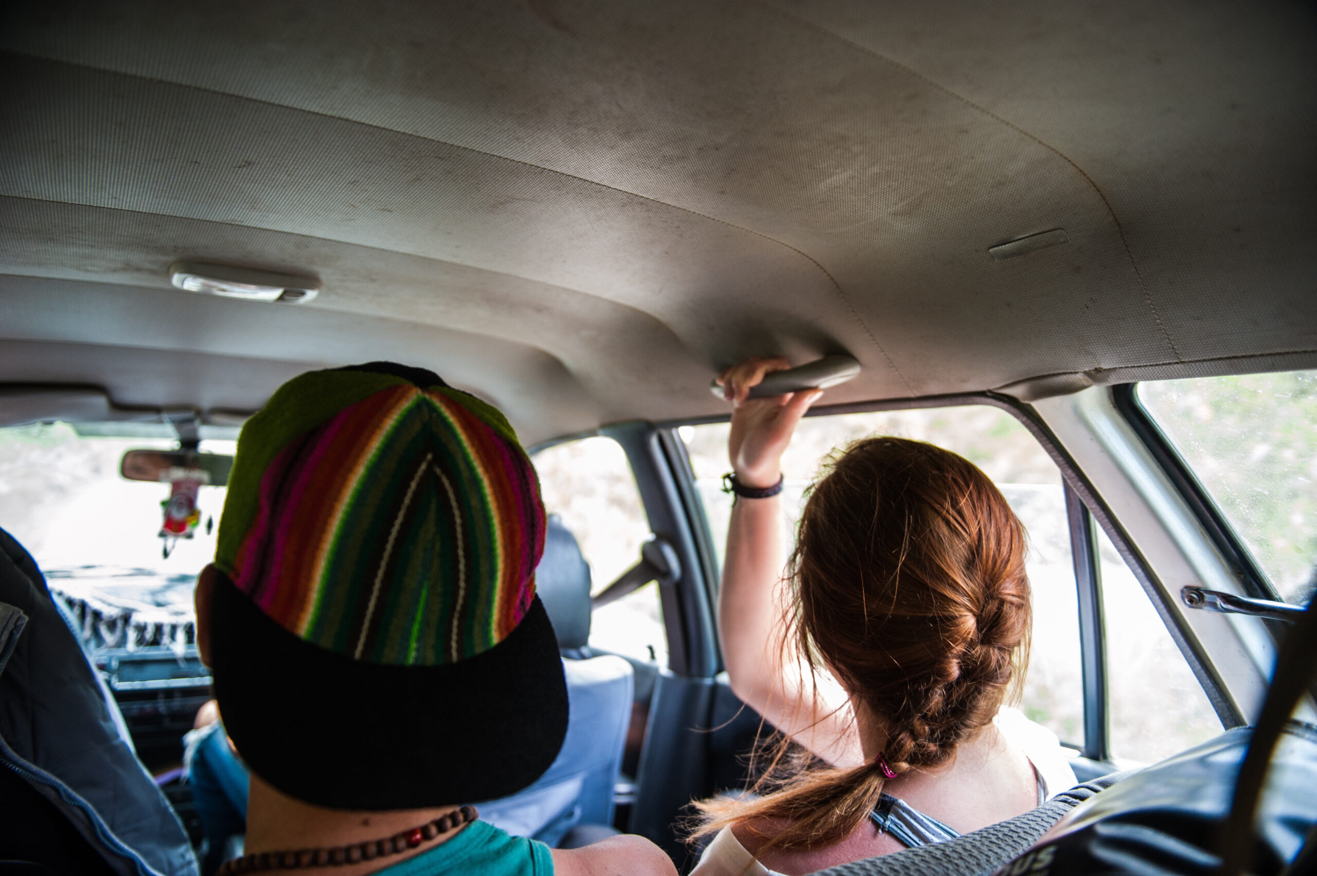 Two passengers in a shared taxi van in peru.