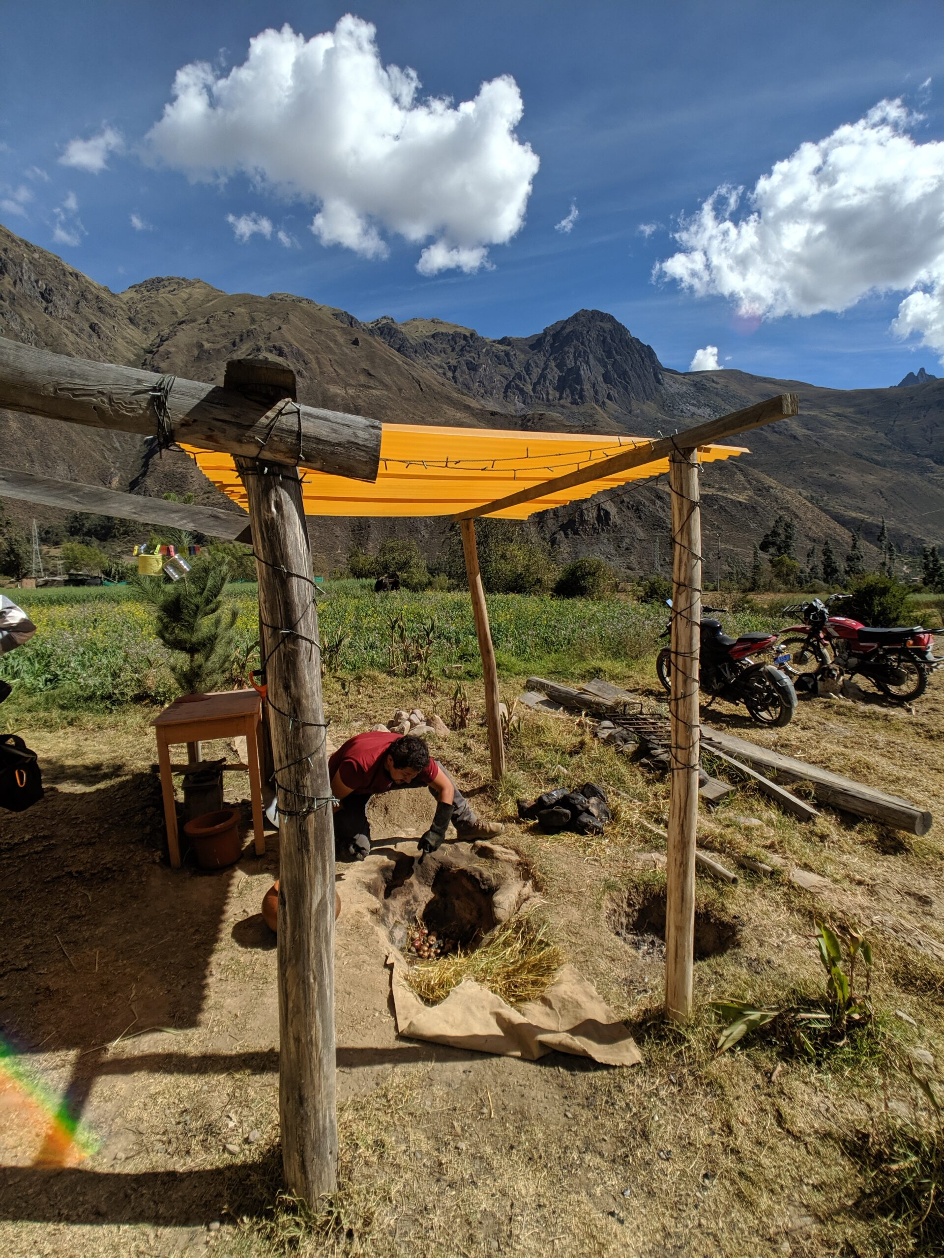 A man works to care for an underground oven under a yellow awning with a backdrop of peruvian mountains.