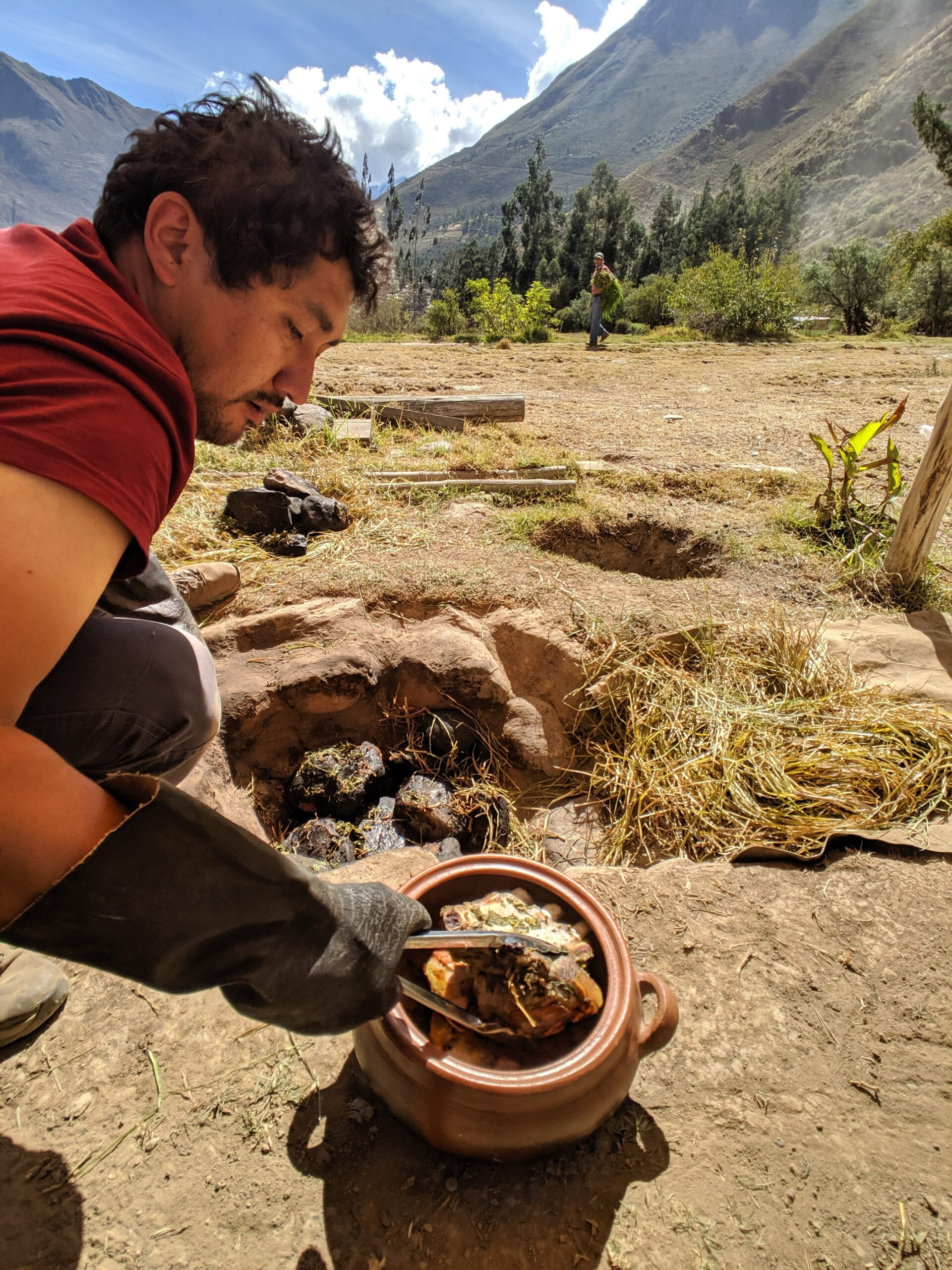 A man pulls meat from a clay oven in peru, photo taken with consent.