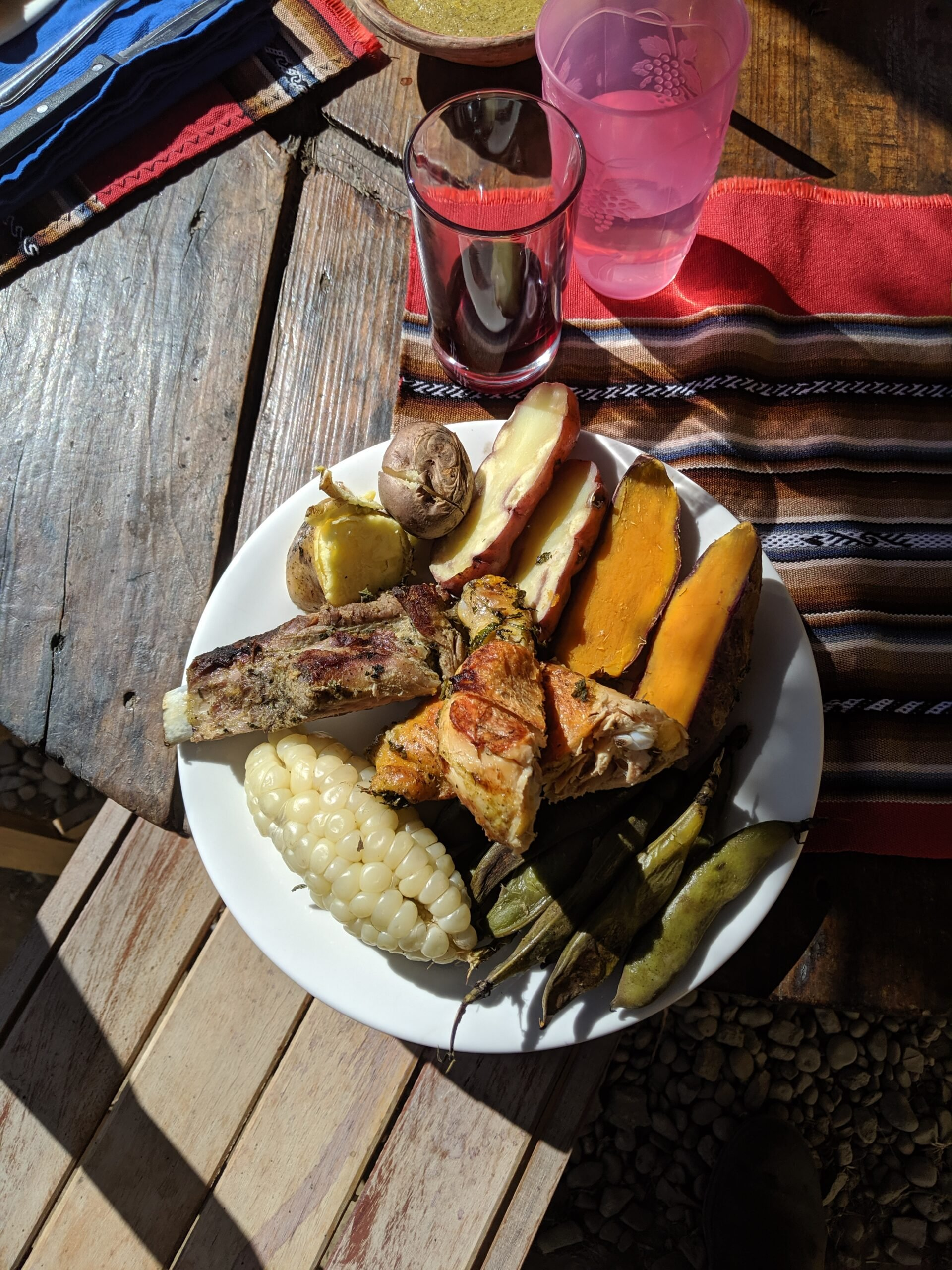 A plate of traditional peruvian meal called a pachamama, containing several kinds of potatoes, chicken, corn, beef ribs, and beans.