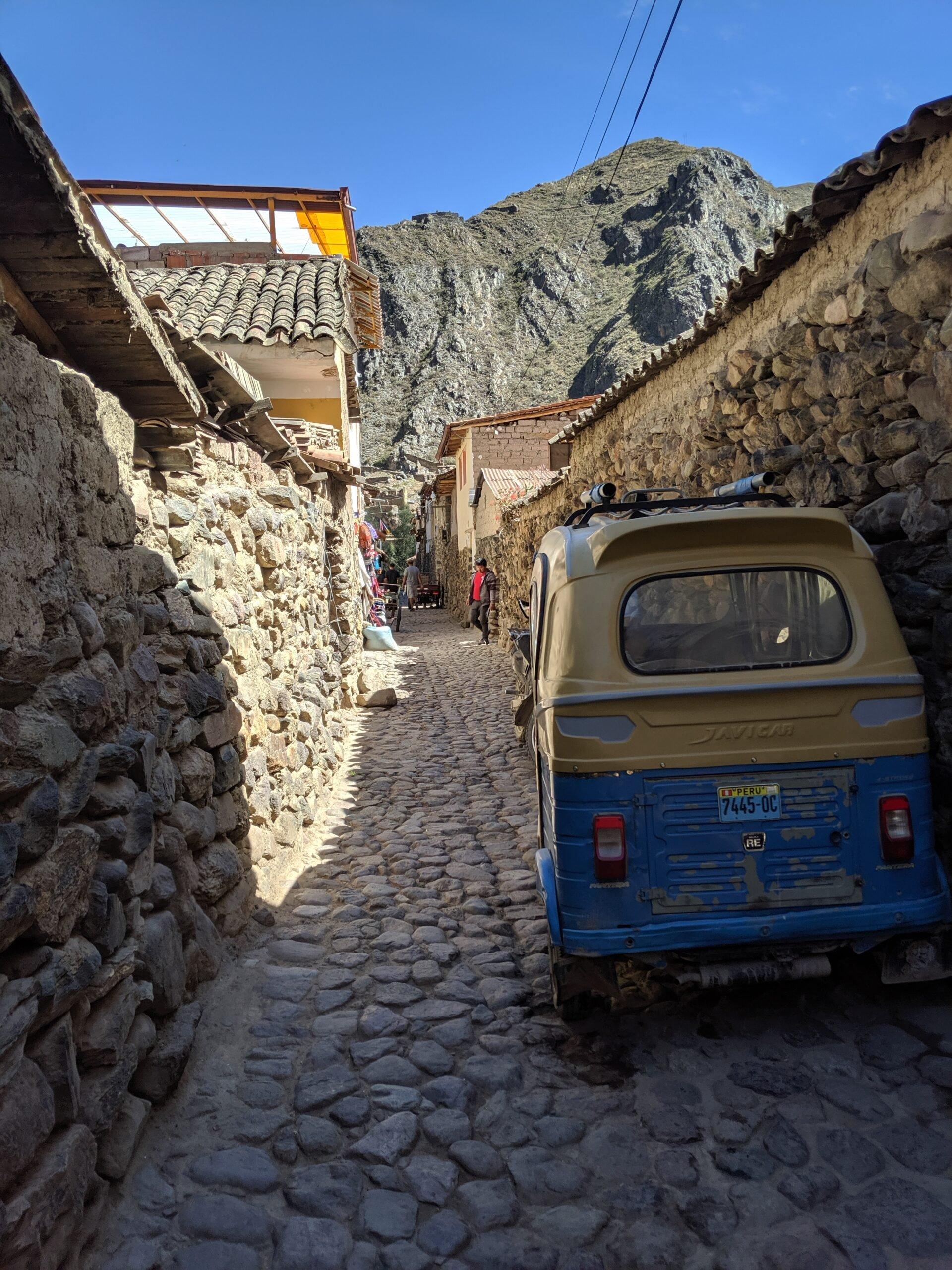 A small van sites in a narrow road in peru.