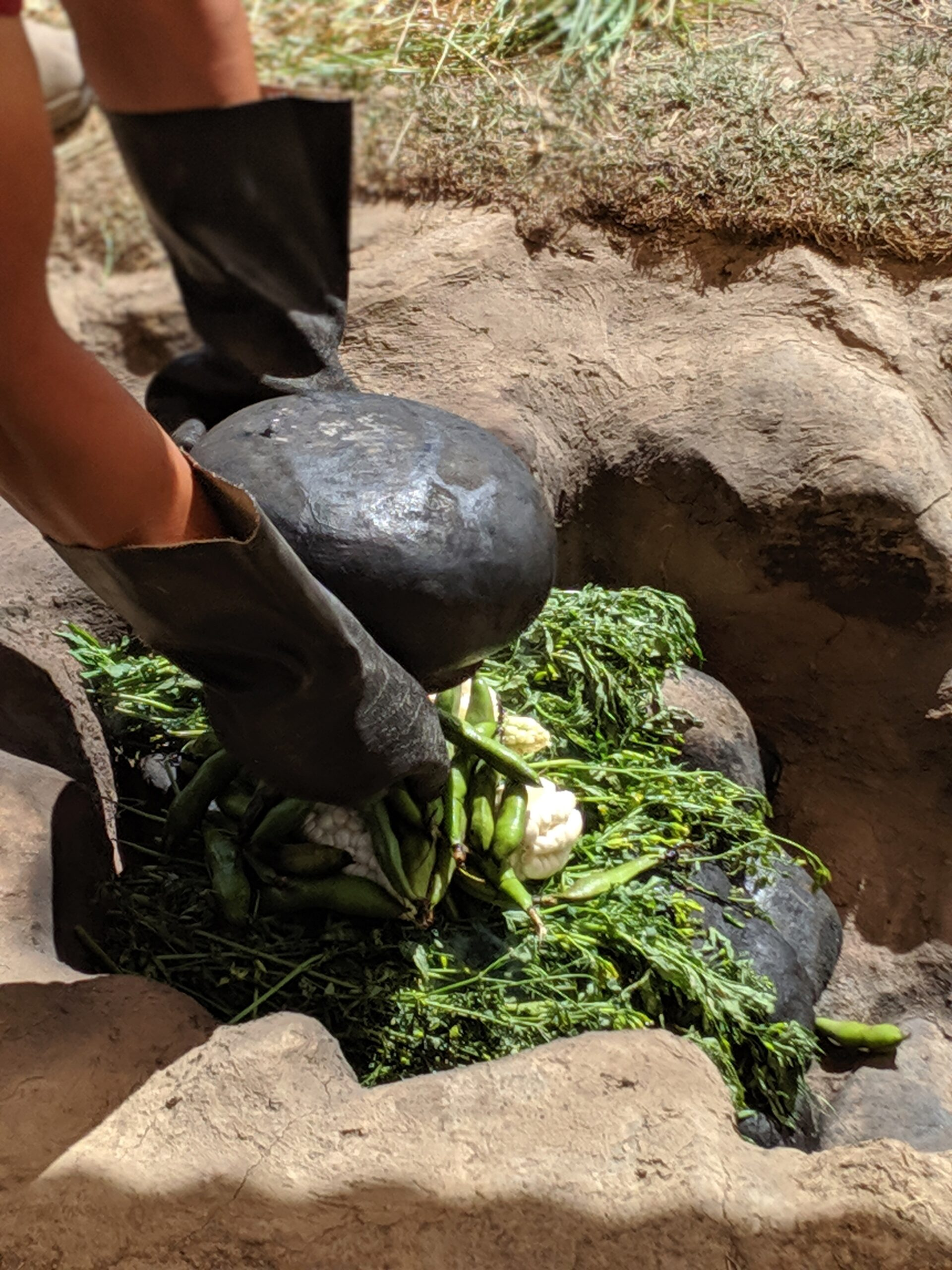 Close-up of a man placing rocks onto a meal cooked in the ground.