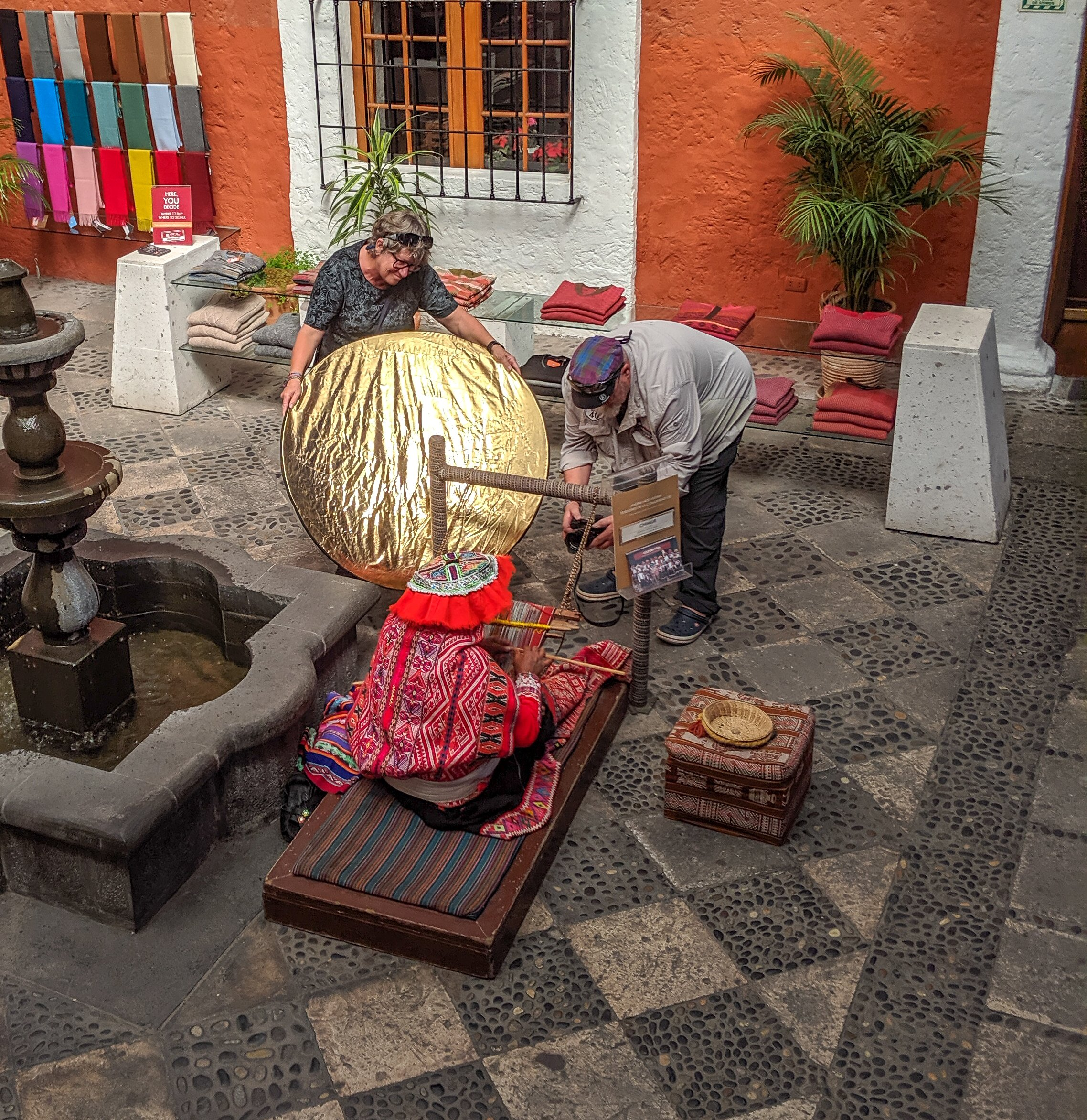 Two western tourists use professional equipment to photograph an indigenous woman in peru.