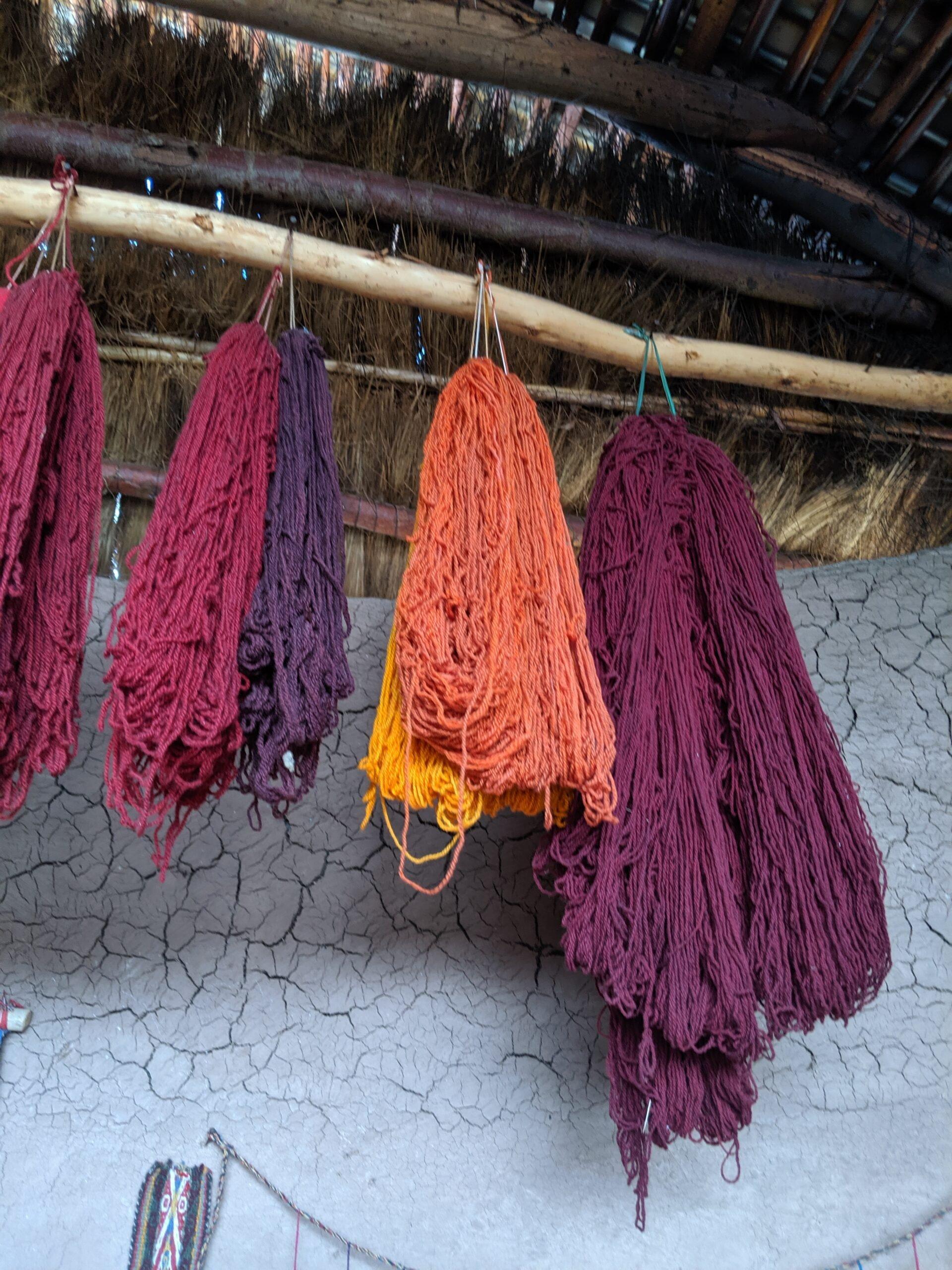 Bundles of freshly dyed yarn hanging to dry in a hut in peru.