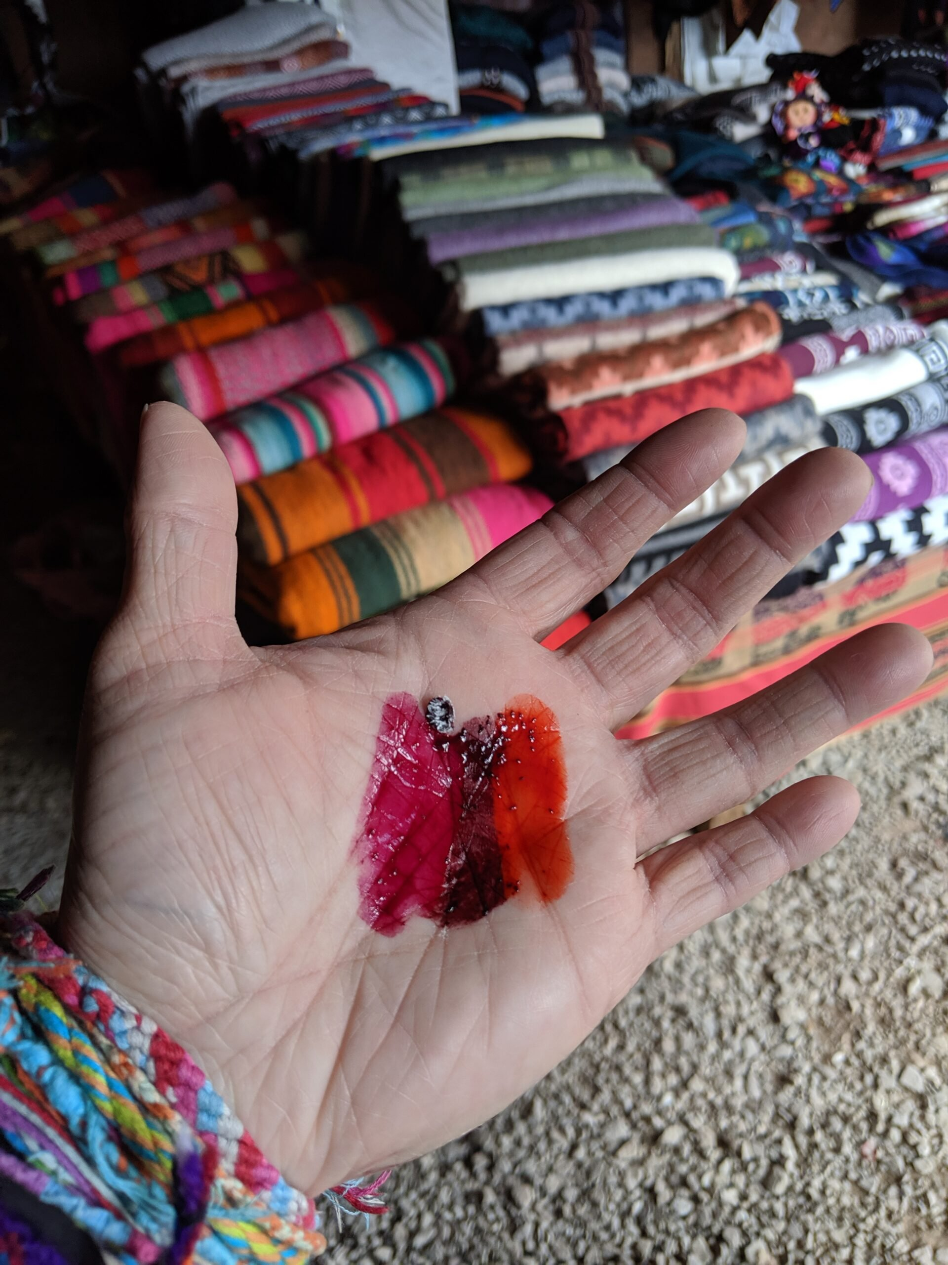 Close-up of a tourist hand showing different dyes used for dying textiles.
