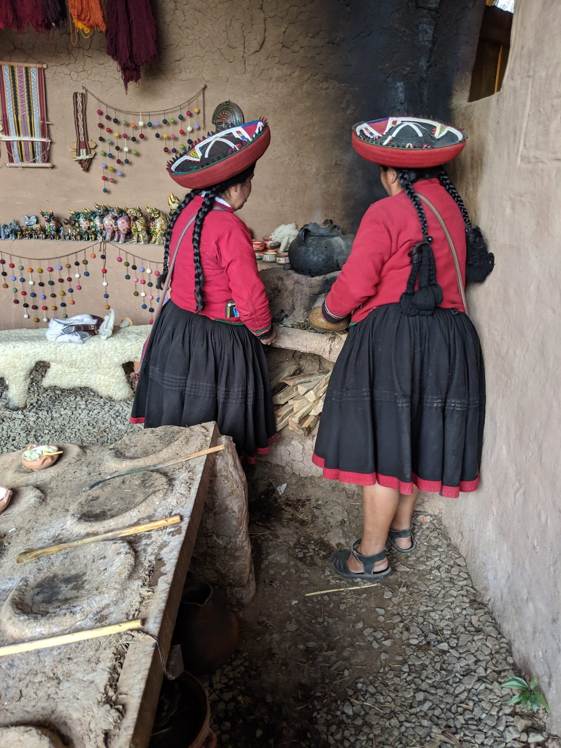 Peruvian women in traditional dress stoking a wood fired stove.