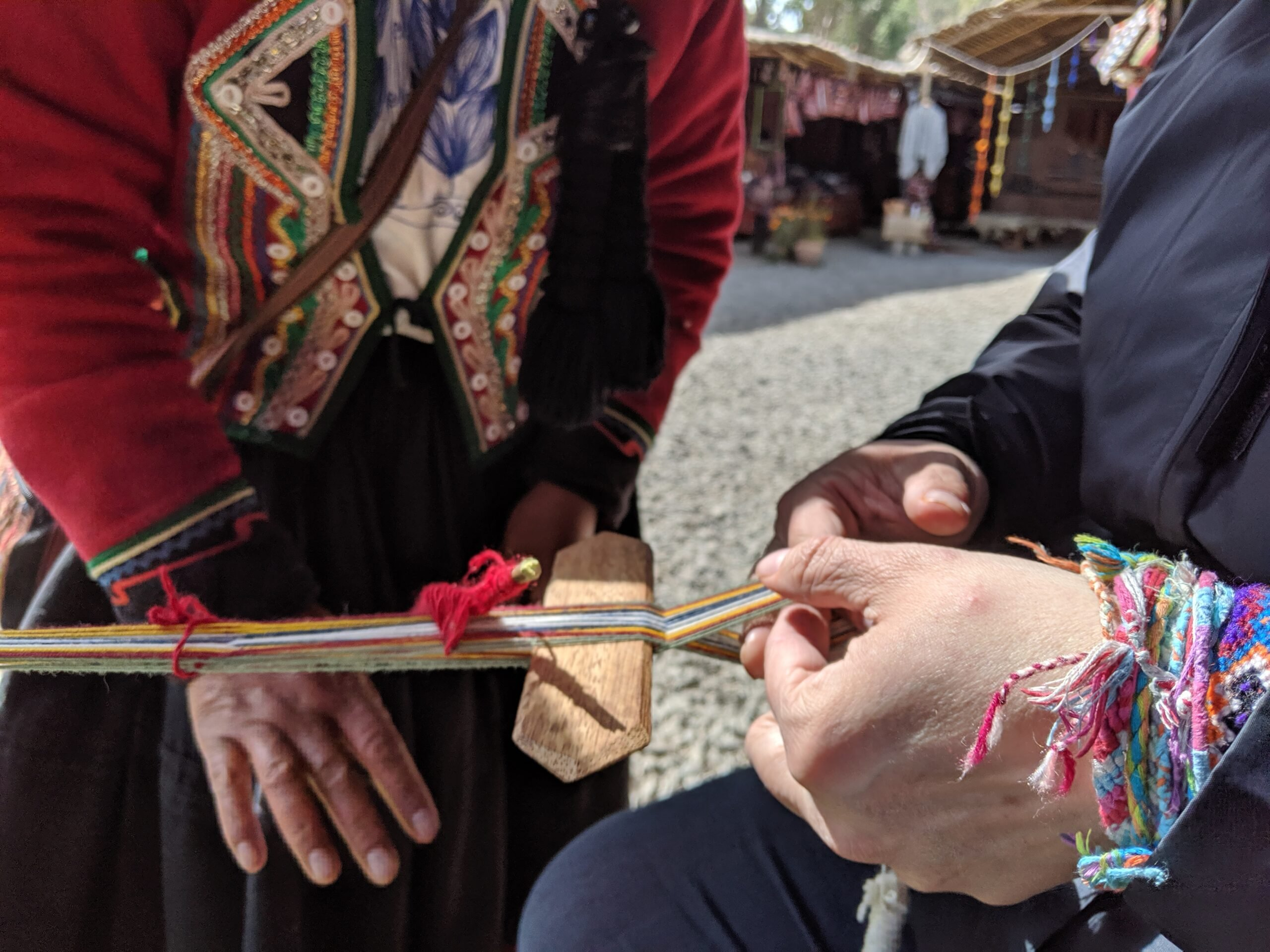 A close-up of hands of a tourist weaving under the instruction of a professional weaver.