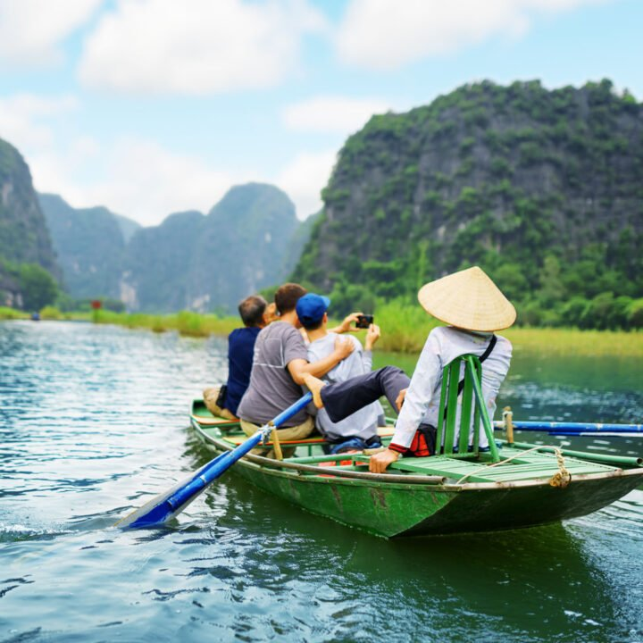 Tourists in a traditional boat in Asia snap a selfie while a tour guide paddles.