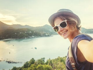 A photo of a woman taking a selfie with a scenic backdrop with the words