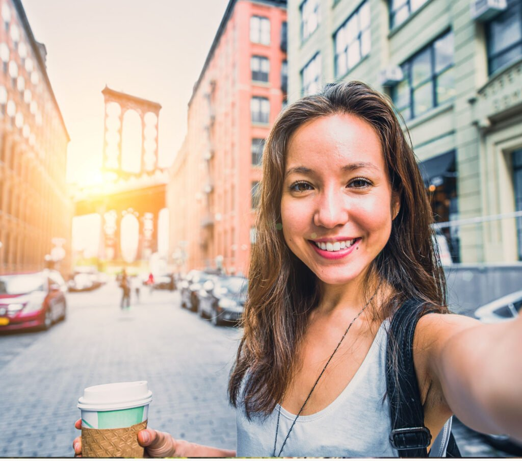 A woman stands in a street in front of the brooklyn bridge and takes a selfie photo.