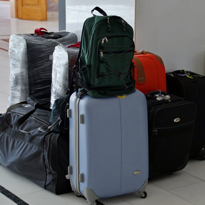 A group of suitcases and backpacks sit in a storage area.