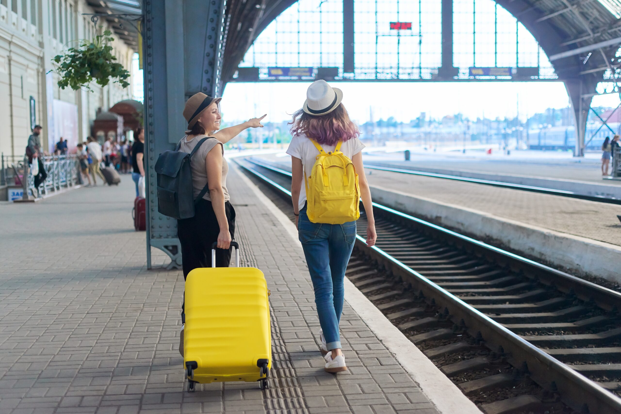 Two woman in a train station, one has a yellow suitcase and the other has a yellow backpack.