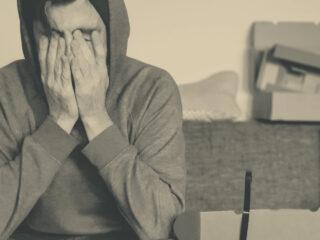 A man in a hoodie rubs his eyes.