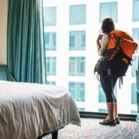 Navigating hostels without friends can be difficult, this image of a woman wearing a backpack staring out a window illustrates this concept.