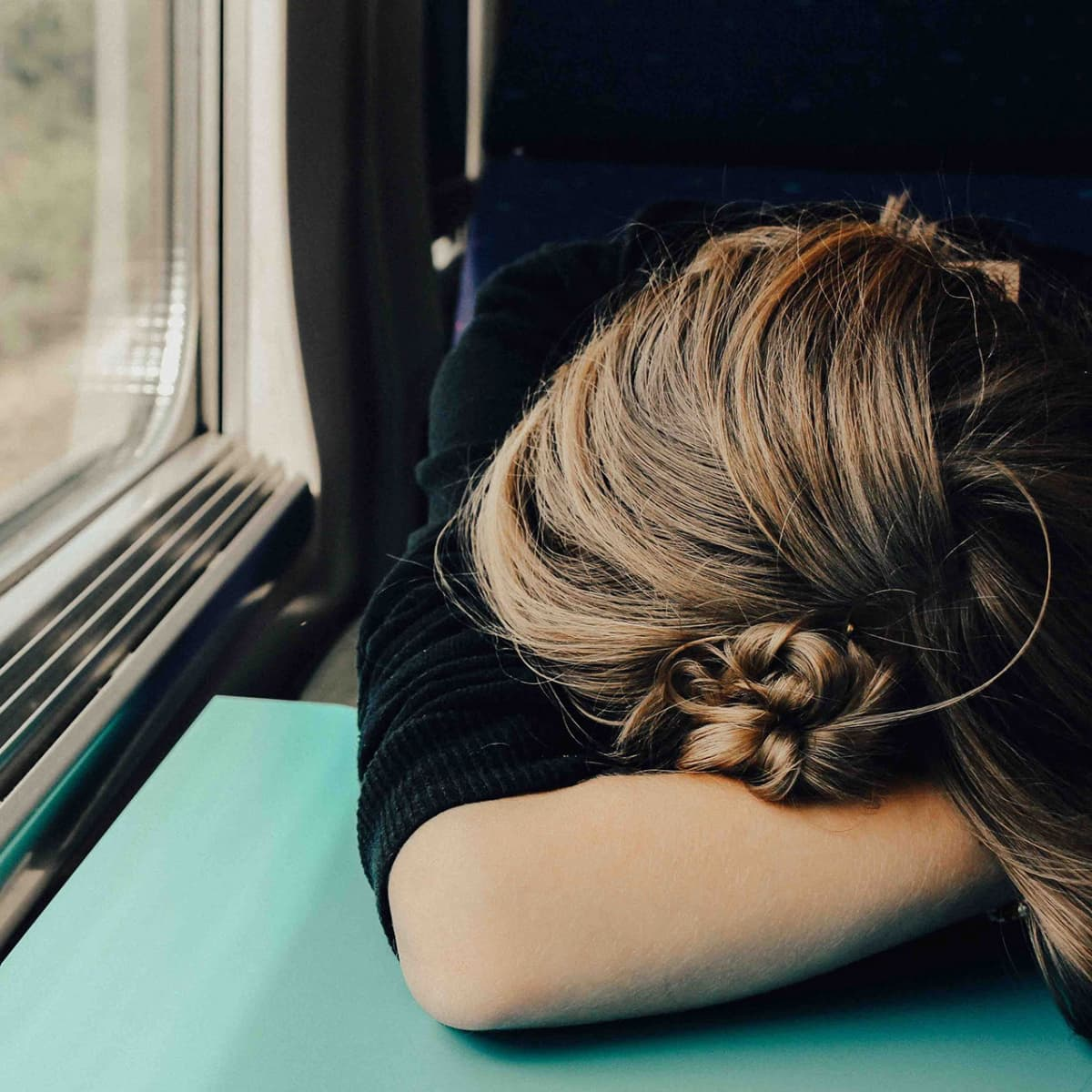 A woman napping on a train.